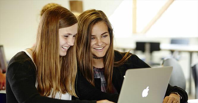 To unge piger sidder ved computer