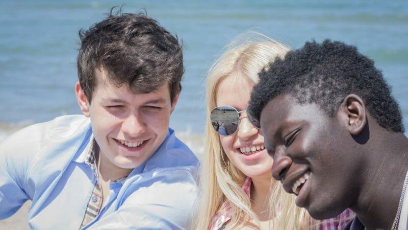 3 personer der sidder ved en strand