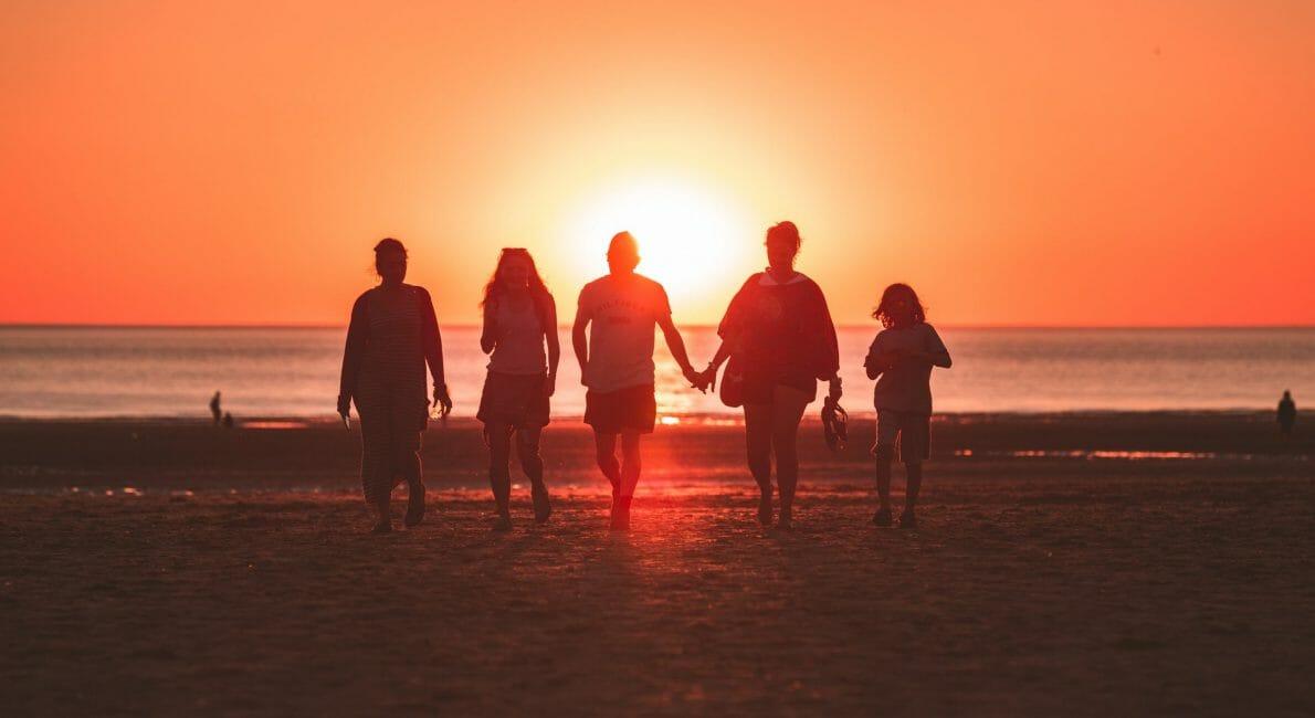 5 mennesker på strand ved solnedgang